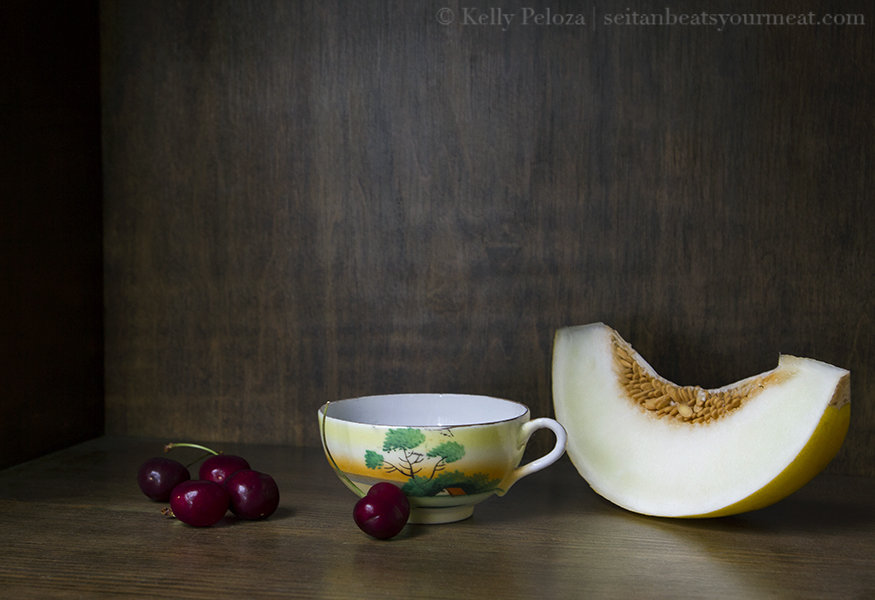 Teacup on wooden shelf with canary melon slice and cherries