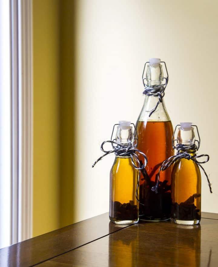 Three bottles of homemade vanilla extract on a table