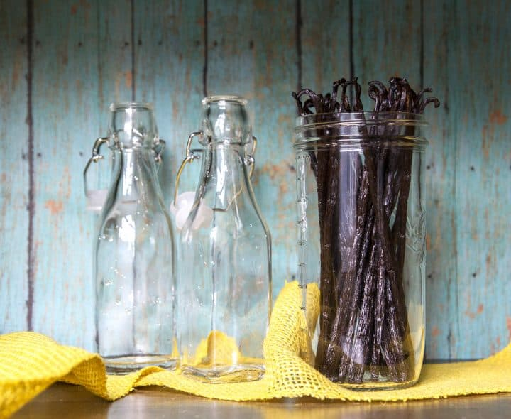Two empty glass bottles next to a mason jar filled with vanilla beans