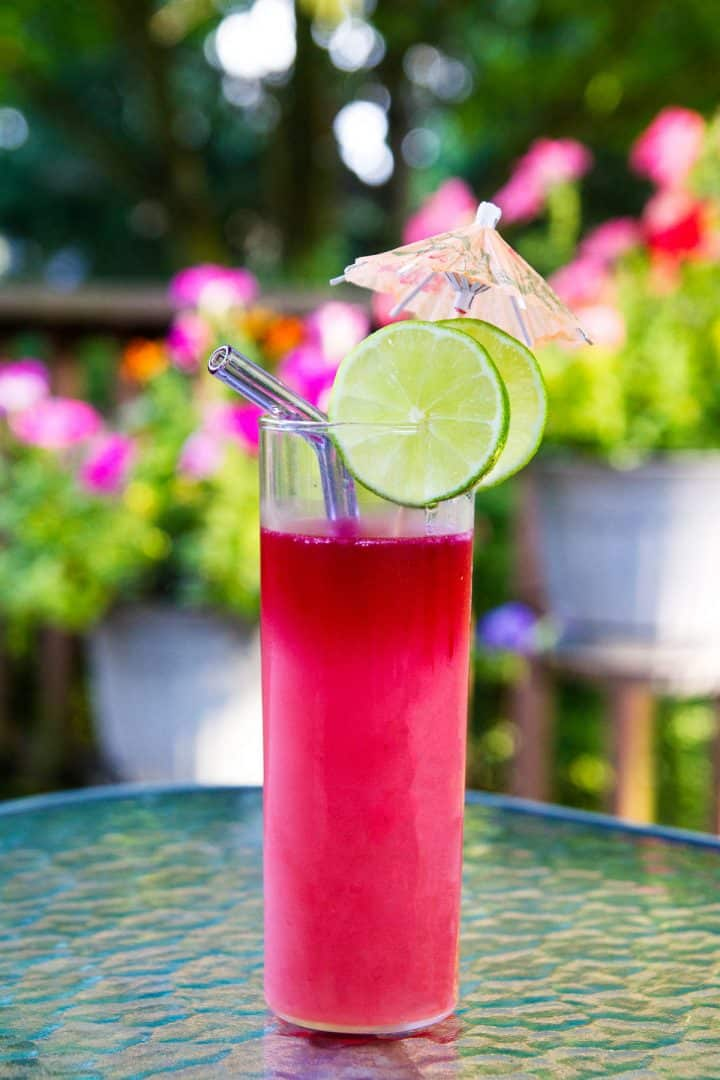 Pink cocktail on table outside with lime slices and cocktail umbrella