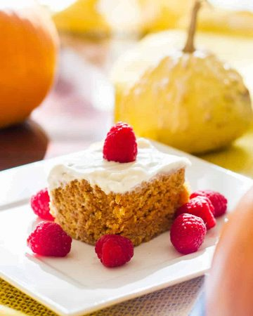 Vegan pumpkin cake with cream cheese frosting on a plate with pumpkins