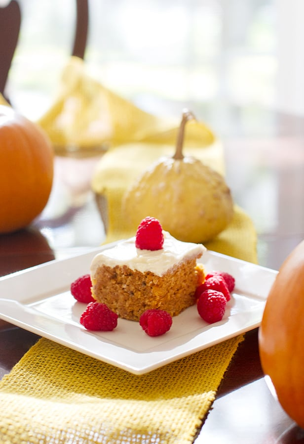 Vertical image of vegan pumpkin cake on a white square plate surrounded by pumpkins