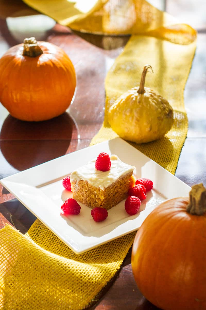 Vertical image of vegan pumpkin cake on a white square plate surrounded by pumpkins and burlap
