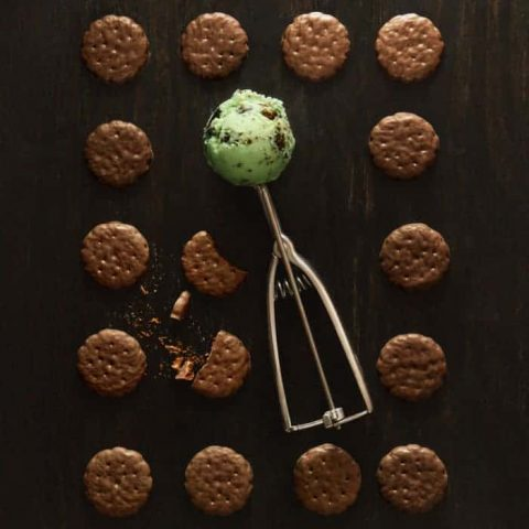 Grid of Thin Mints on black background with green ice cream in ice cream scoop in center