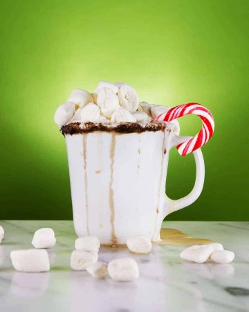 Mug with marshmallows on marble counter with green background