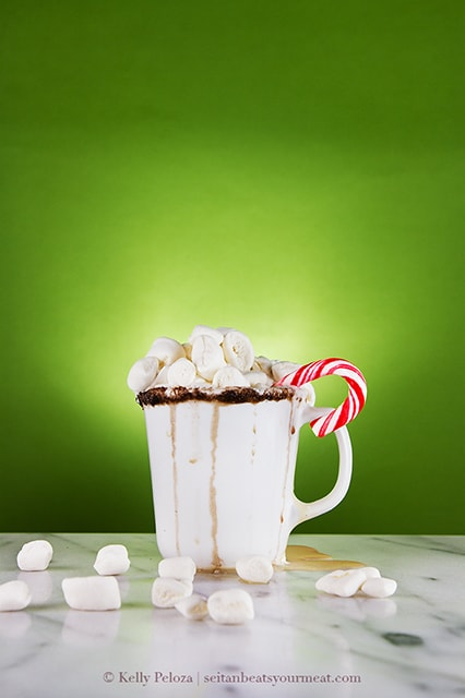 Overflowing mug of white russian hot chocolate on a marble surface with a green background