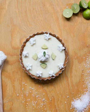 Key lime pie with limes on wooden counter