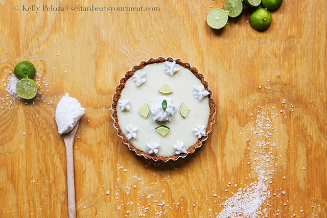Key lime pie on wooden counter surrounded by limes and salt