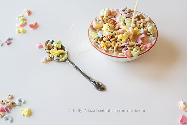 Bowl of Vegan Lucky Charms on white table with spoonful of cereal next to bowl