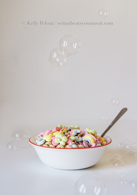Bowl of Vegan Lucky Charms on white table with bubbles in the air