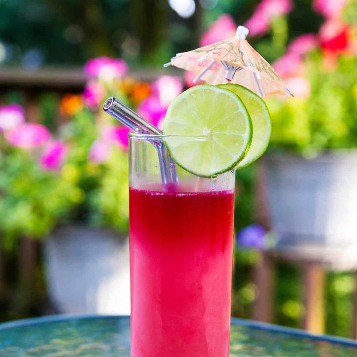 Pink cocktail on outdoor table with flowers