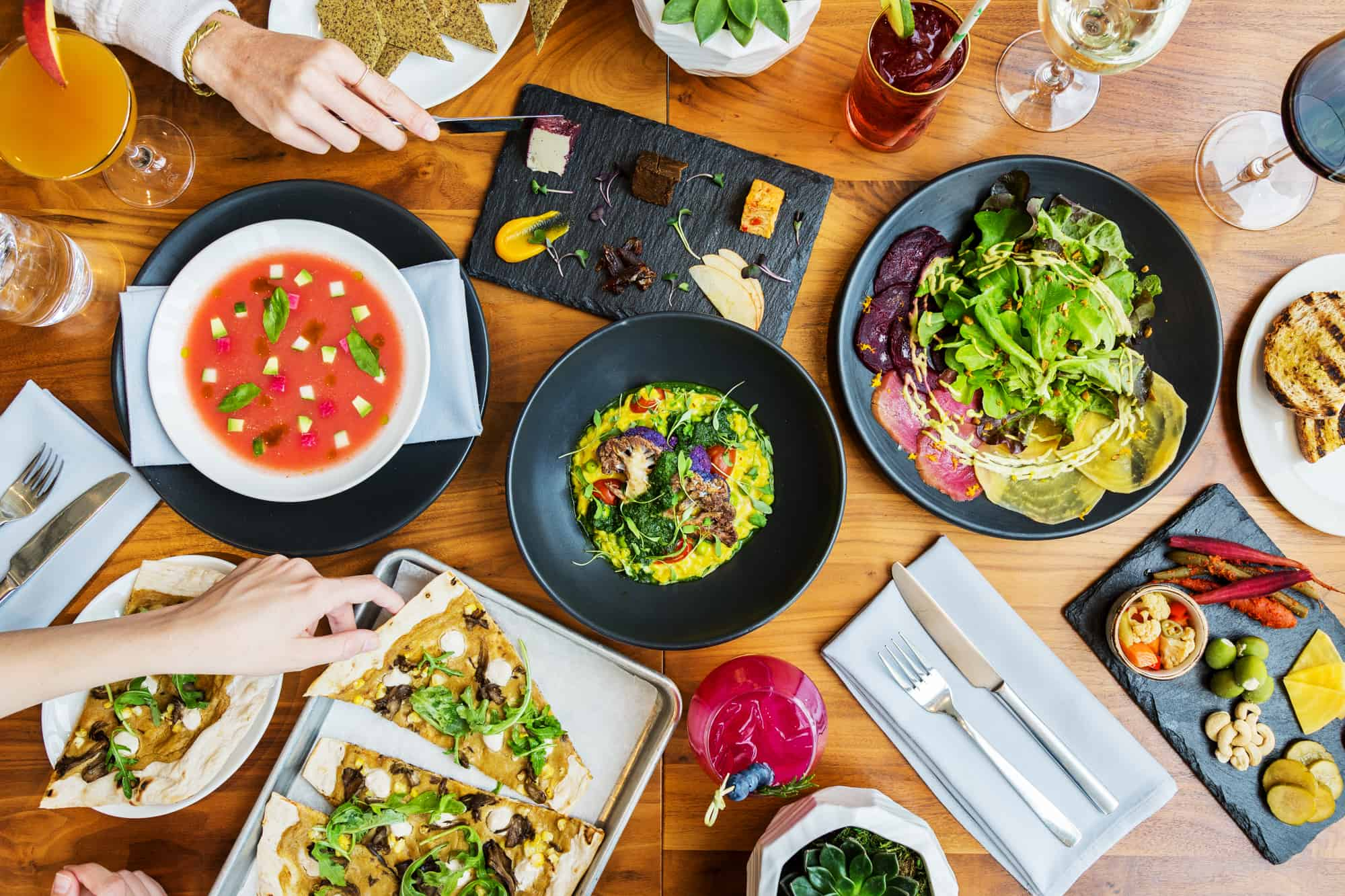 Overhead photo of plant-based dishes and cocktails at Althea