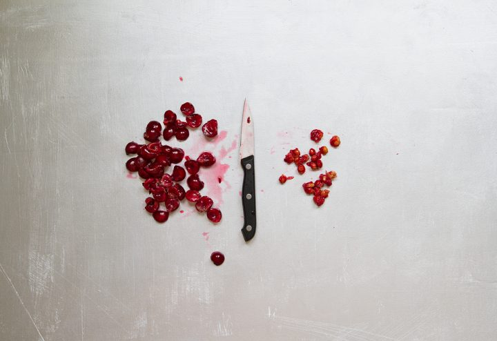 Paring knife with pile of pitted cherries on the left and cherry pits on the right