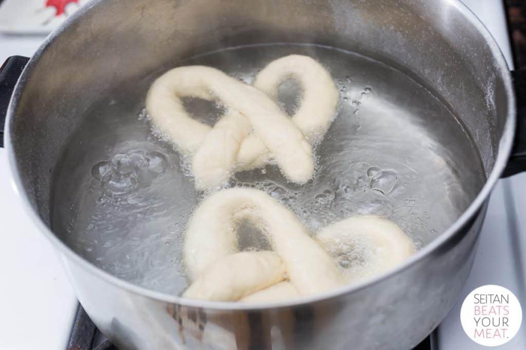 Two soft pretzels boiling in a baking soda bath