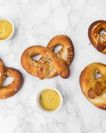 Soft pretzels on a marble counter with cups of mustard