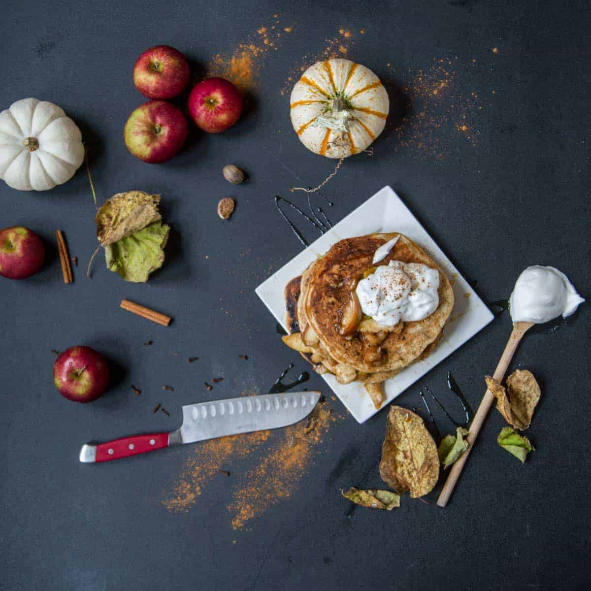 Apple pie pancakes on black background surrounded by apples