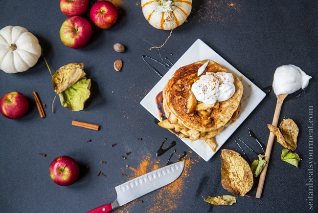 Apple pancakes on a plate surrounded by apples and leaves