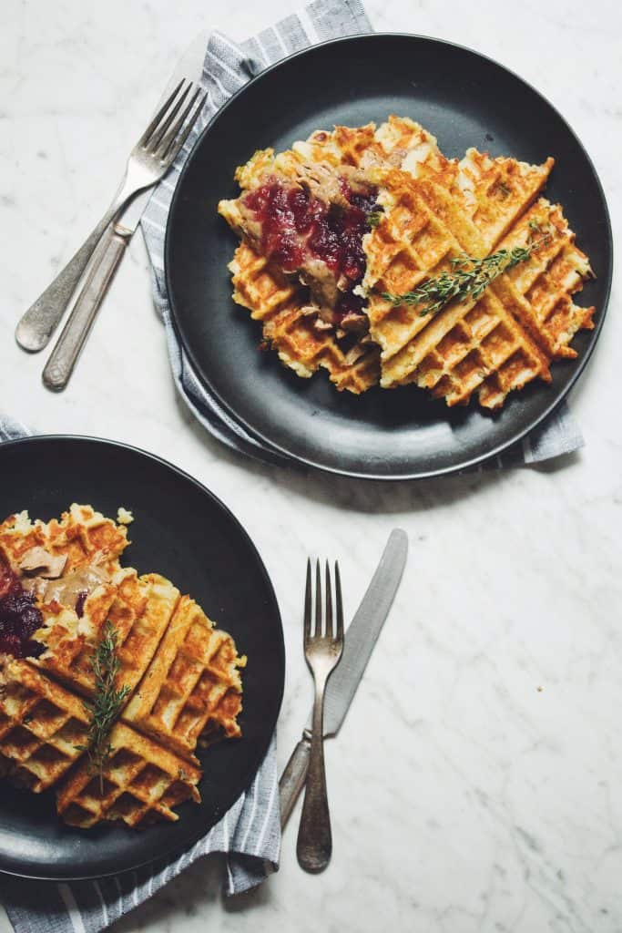 Two plates of dinner waffles on marble surface with silverware
