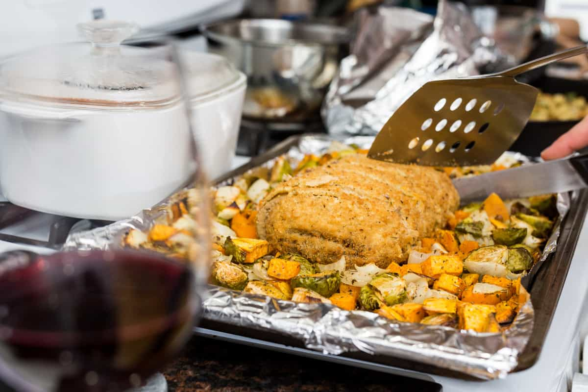 Trader Joe's Turkeyless Roast being cut on a baking sheet surrounded by vegetables