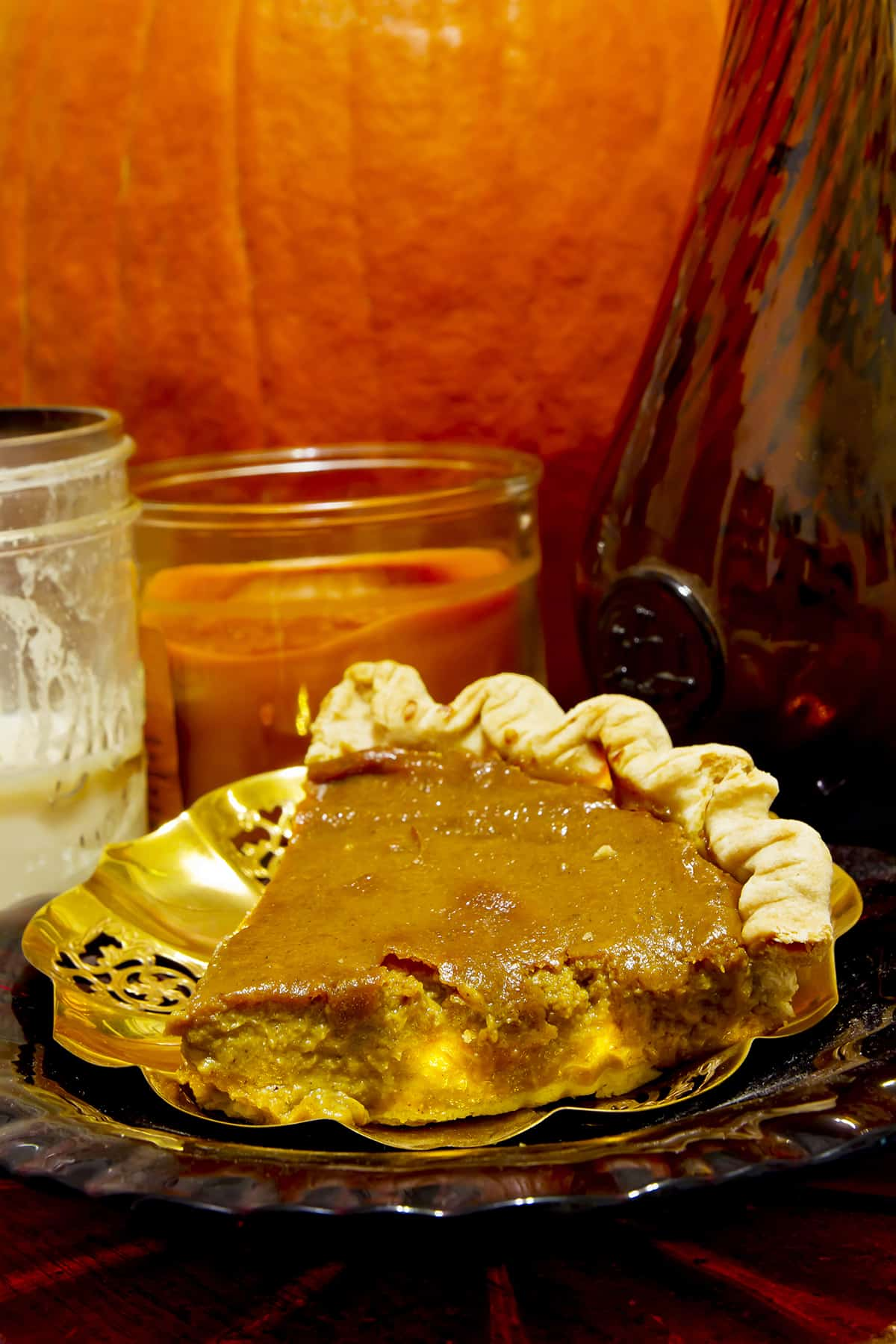 Pumpkin pie on gold plate surrounded by candles and pumpkins