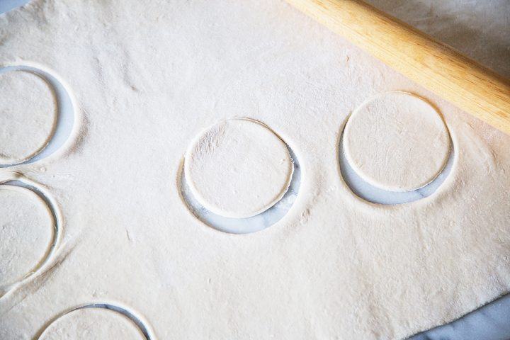 Rolled out pierogi dough with 3 inch circles cut out