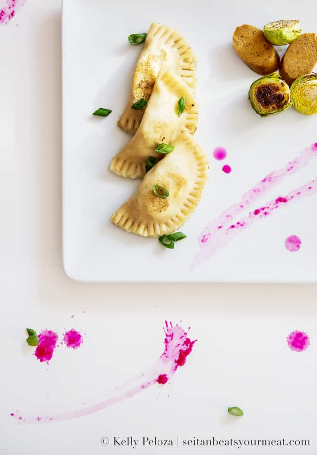 Overhead close up image of vegan potato and onion pierogi with beet horseradish and Brussels sprouts