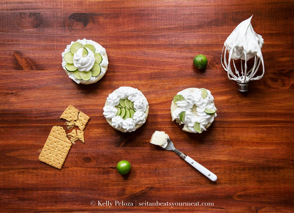 Small key lime pies with meringue topping on wooden counter