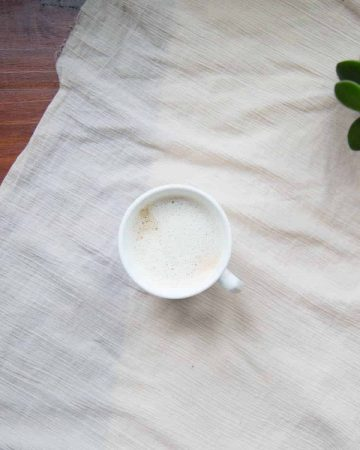Mug of cashew milk on cream tablecloth