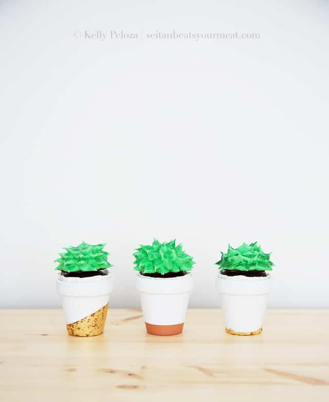 Three succulent cupcakes in small terra cotta pots on wood table