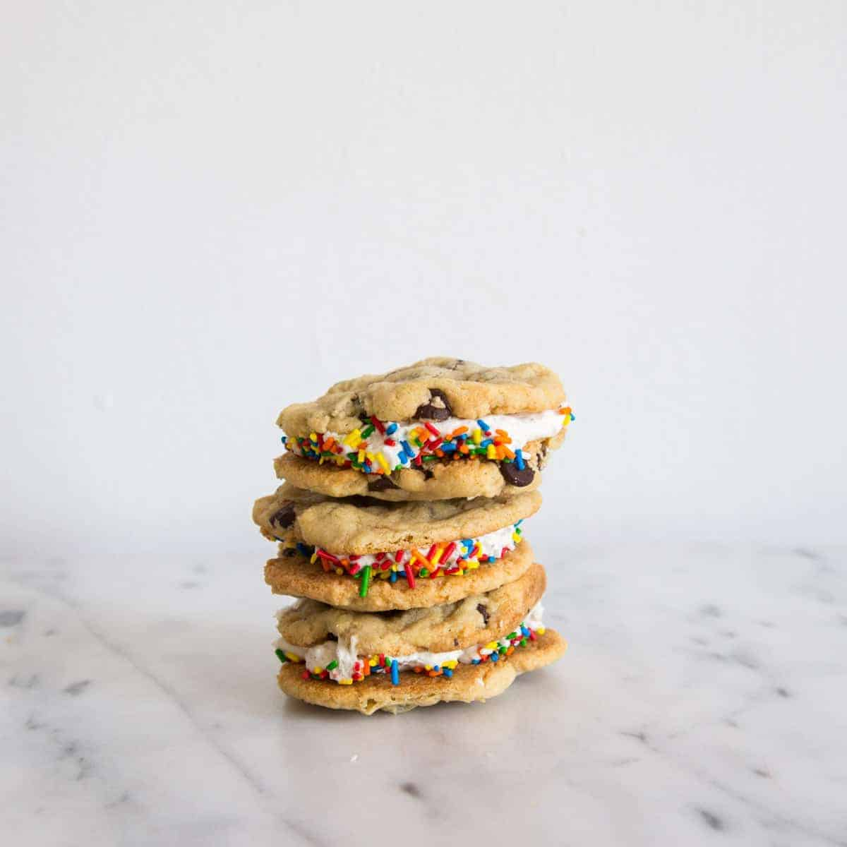 Stack of chocolate chip cookie sandwiches with Oreo buttercream on marble table