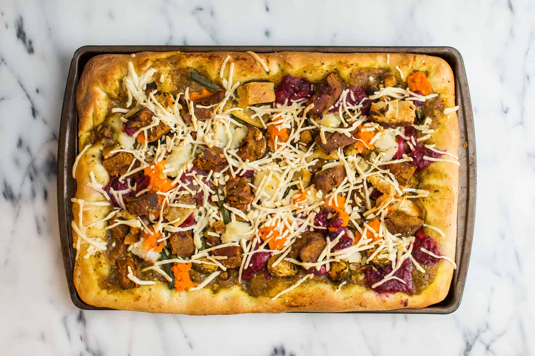 Overhead image of Thanksgiving pizza in pan on marble surface
