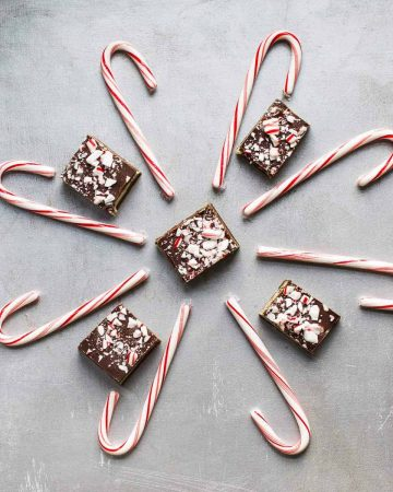 Five chocolate peppermint bars surrounded by candy canes in a snowflake shape