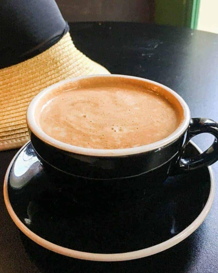 Cafe latte on table with hat in background