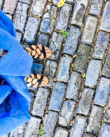 Feet in sandals on blue cobblestone