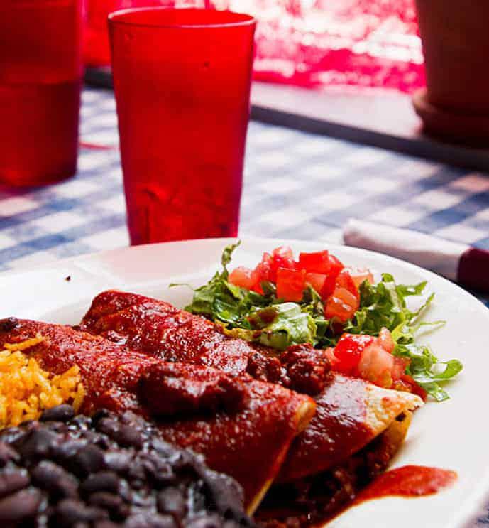 Plate of vegan enchiladas and salad at a restaurant