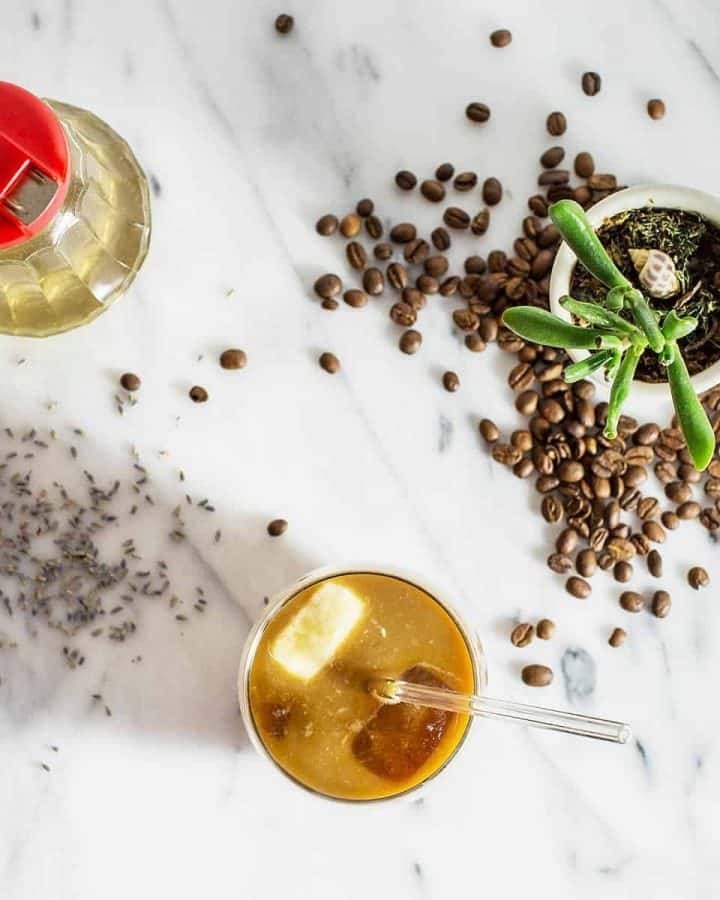 Cold brew coffee in glass on marble surface with coffee beans and potted plant