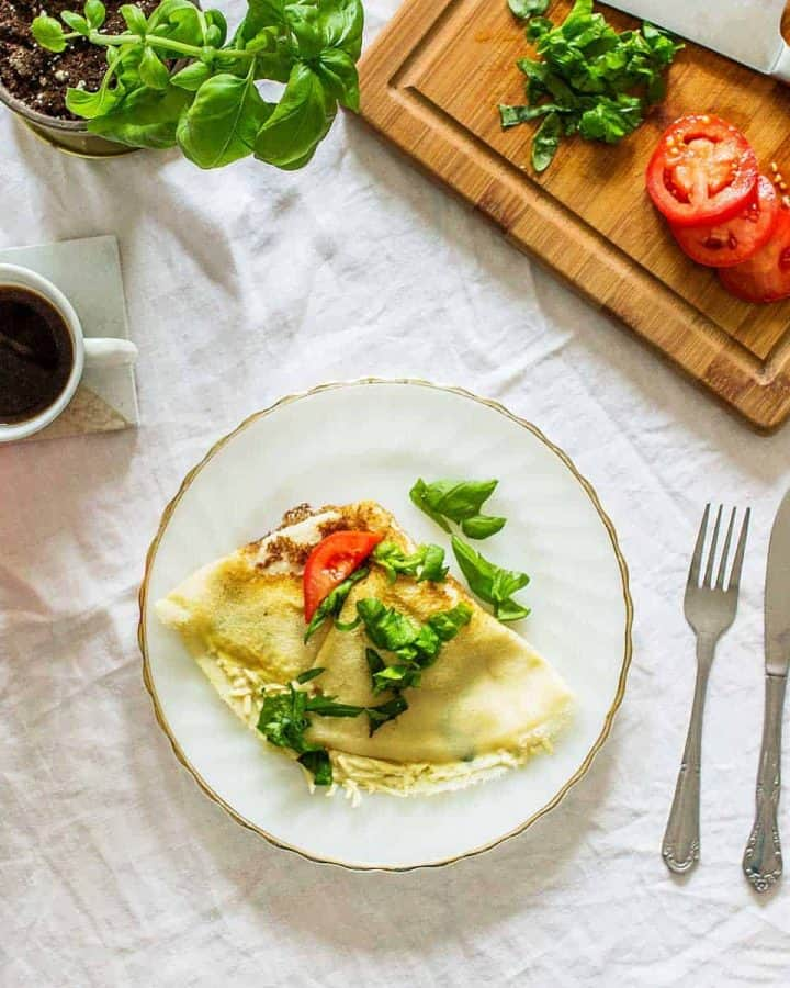 Crepe with tomato and basil on white and gold plate on white tablecloth