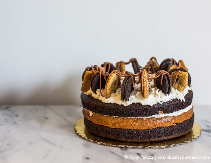 Triple layer chocolate cake topped with cookies on marble counter