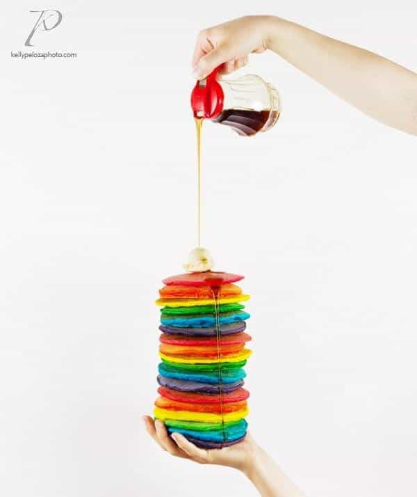 Tall stack of rainbow pancakes sitting in a hand with another hand pouring syrup on the pancakes