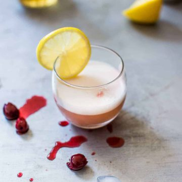 Close up photo of whiskey sour on silver counter surrounded by cherries and lemons