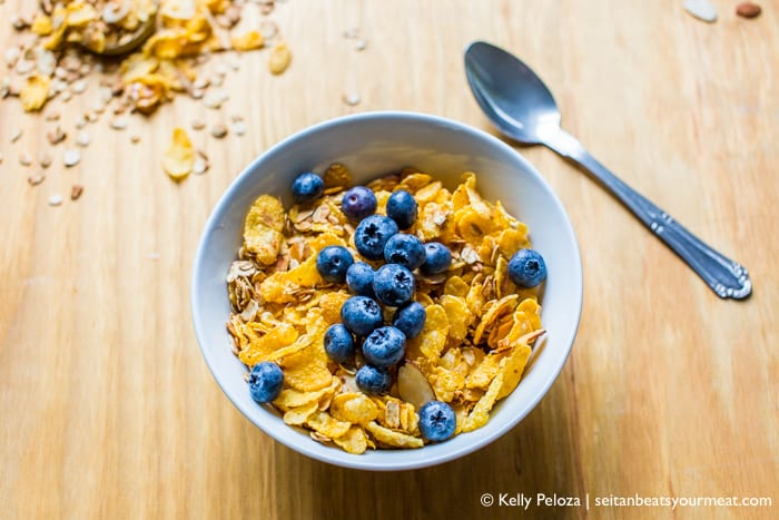 Bowl of vegan Honey Bunches of Oats cereal in bowl with blueberries on a wooden counter