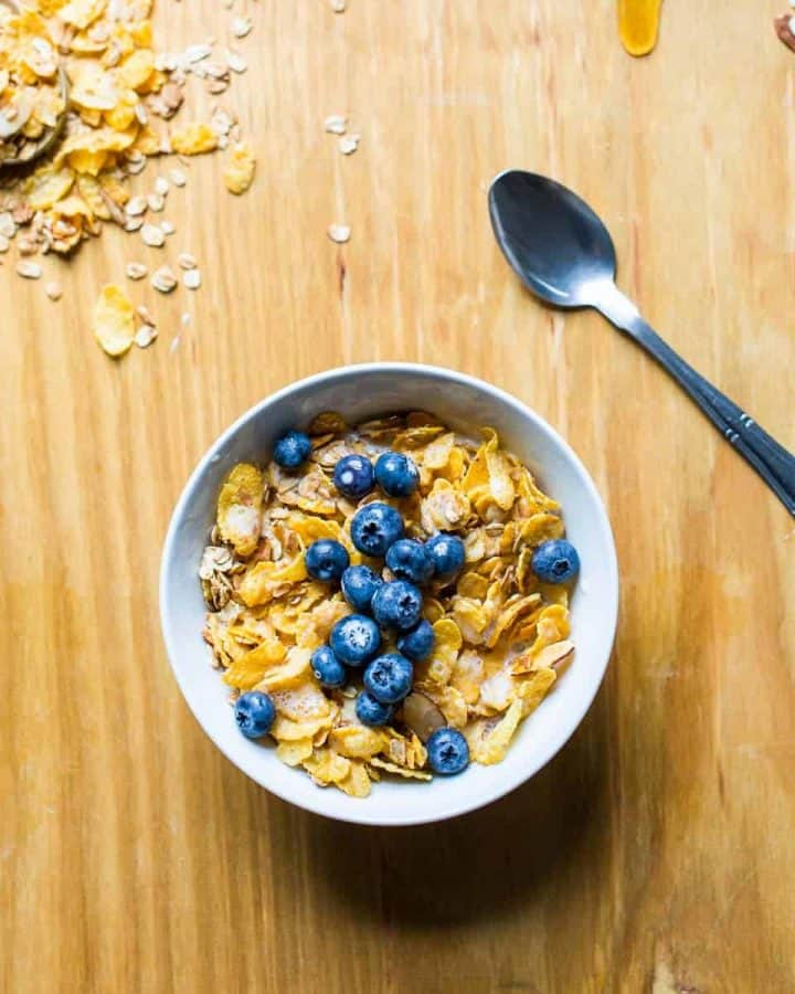 Bowl of vegan Honey Bunches of Oats with blueberries on wooden surface