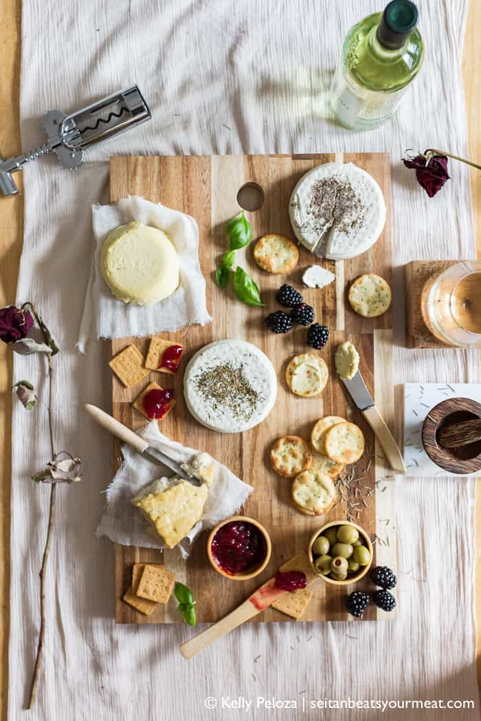 Ovehead image of vegan cheese board surrounded by wine and decor