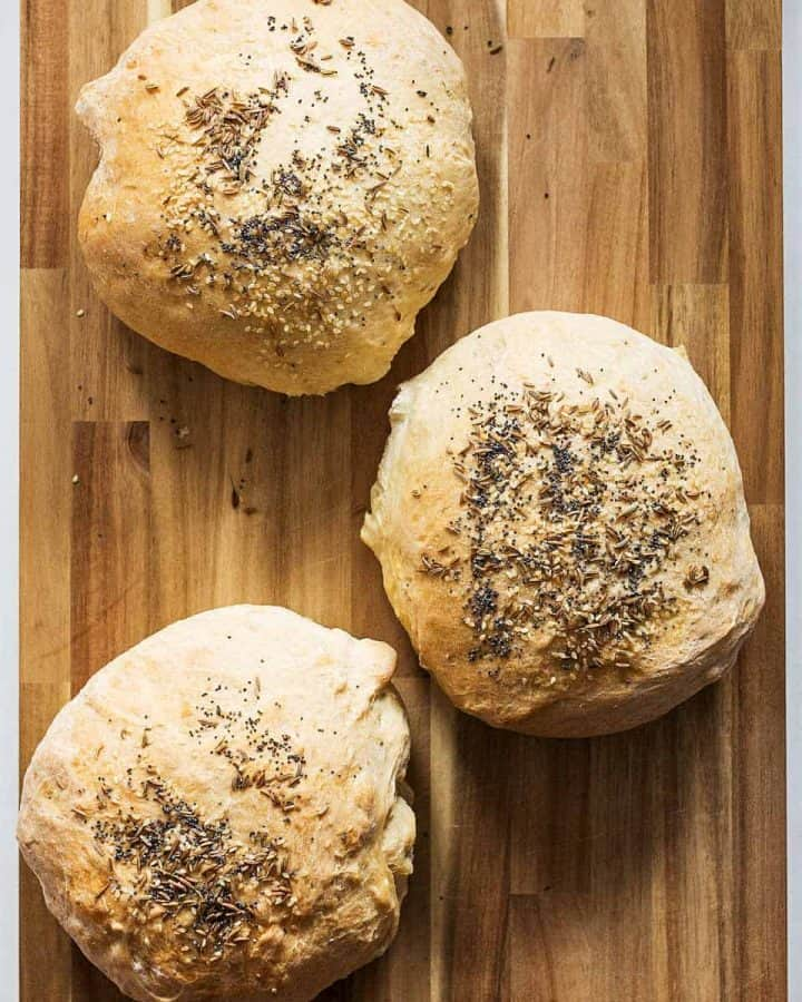 Three small round loaves of bread with caraway seeds on wooden cutting board
