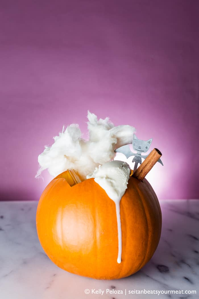 Pumpkin milkshake served in pie pumpkin on marble counter with purple background