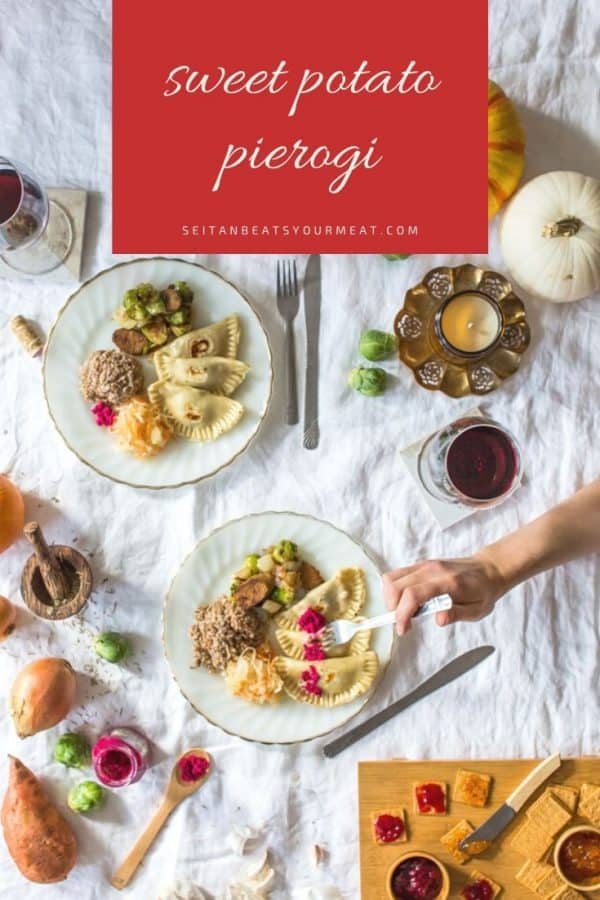 Wide overhead image of sweet potato pierogi on plates surrounded by fall decor and wine