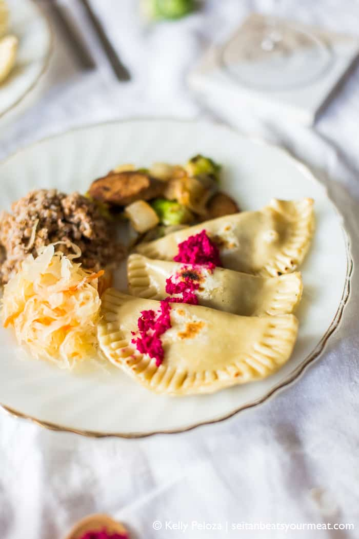 White dinner plate with sweet potato pierogi, sauerkraut, roasted Brussels sprouts, and kasha on white background