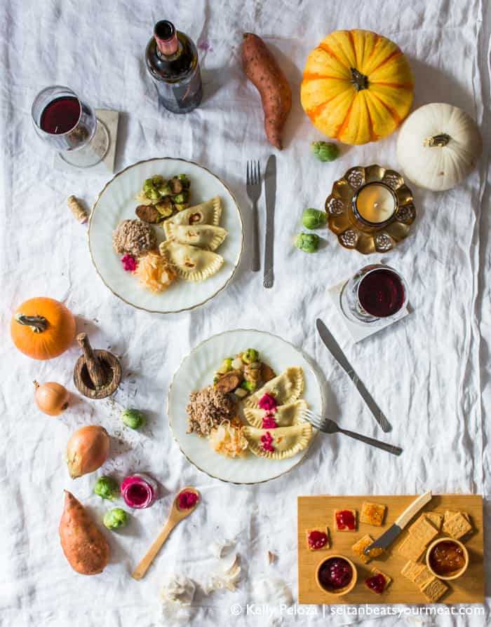 Wide overhead image of dinner plates with sweet potato pierogi, sauerkraut, kasha, and roasted Brussels sprouts, surrounded by ingredients and wine on a white tablecloth