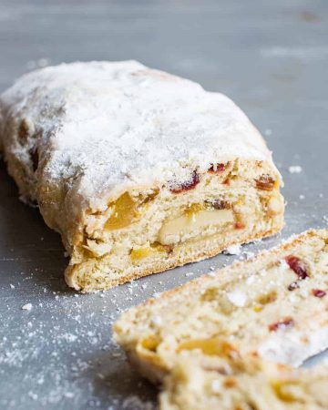 Vegan stollen loaf cut open showing marzipan inside on silver counter