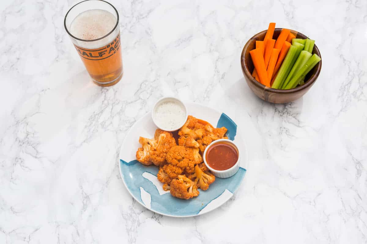 Plate of buffalo cauliflower on marble background with bowl of carrot and celery sticks and beer in pint glass